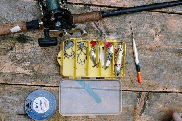 Fishing tackle laid out on a wooden floor outdoor