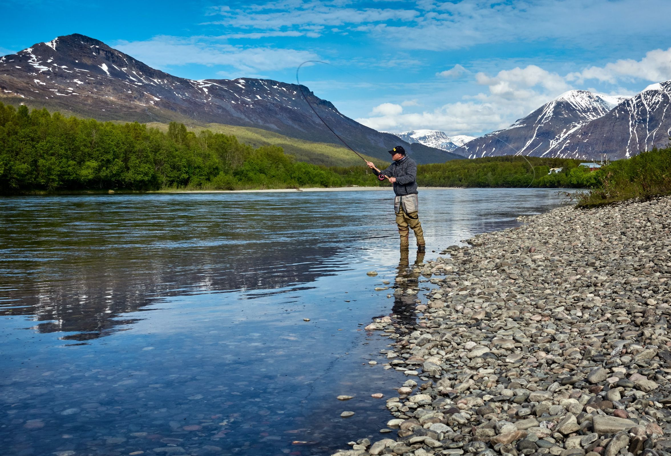 Man fishing on the shallow part of the river with the view of the mountains