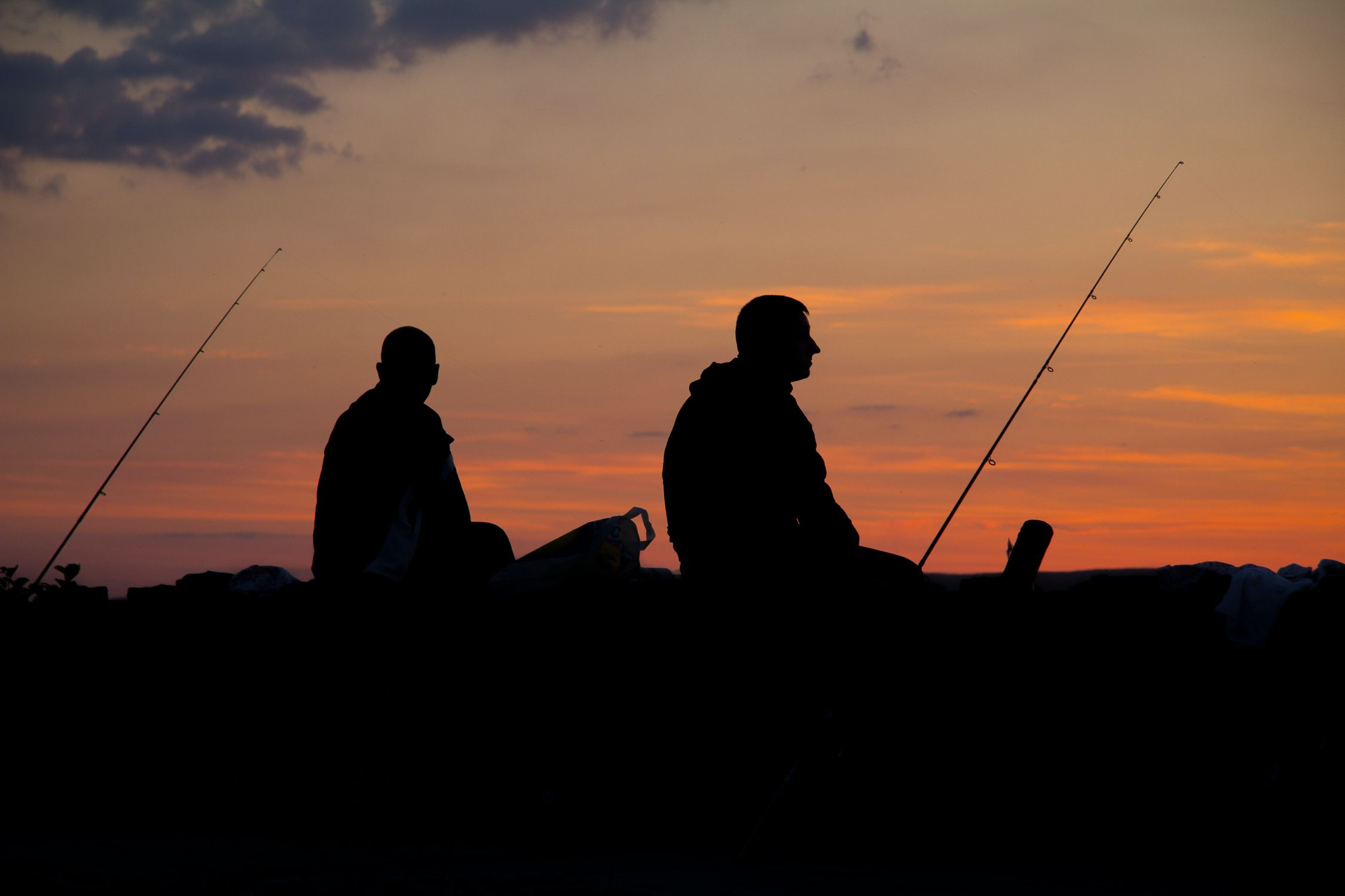 Silhouette of two men fishing at sunset